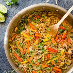 vegetarian thai peanut pasta in skillet with wooden spoon