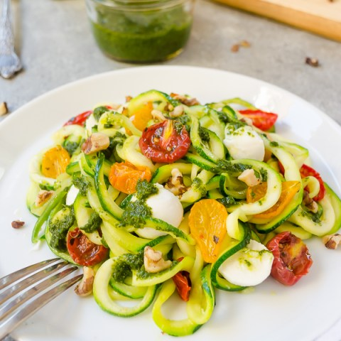Pesto zoodles on white plate with fork