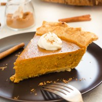 chai pumpkin pie on a plate with whipped cream