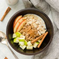 Quinoa breakfast bowls with apples and cinnamon sticks on top