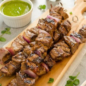 honey soy steak kebabs on a cutting board with cilantro lime sauce