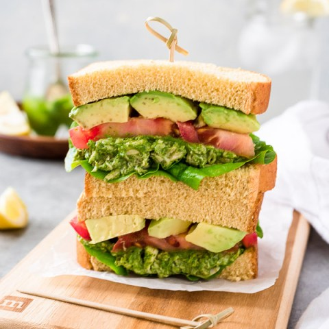 pesto chicken salad sandwiches stacked up on a cutting board