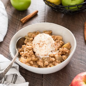 apple pear crisp serving in bowl topped with ice cream