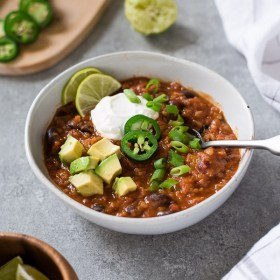 Lentil chili front view with spoon dipped into bowl
