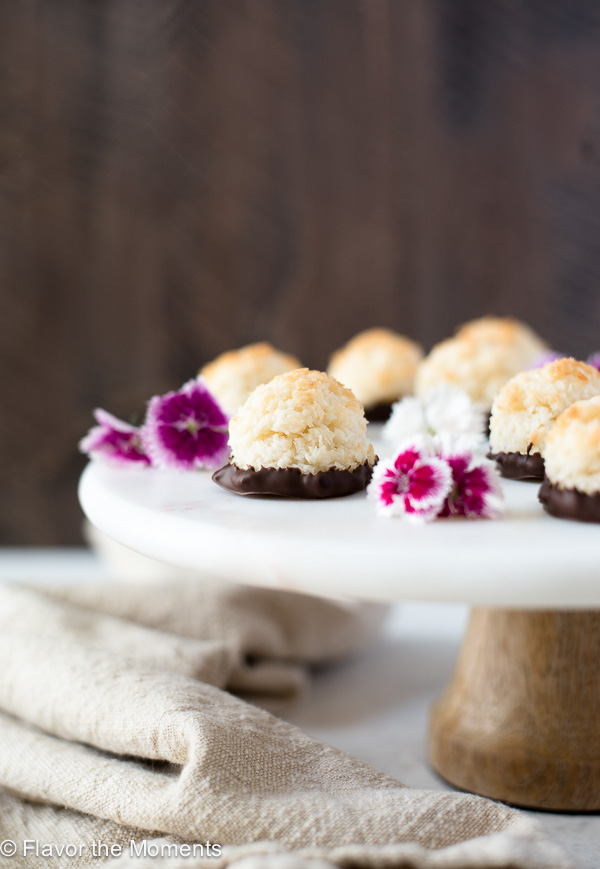 coconut macaroons on pedestal with edible flowers front view