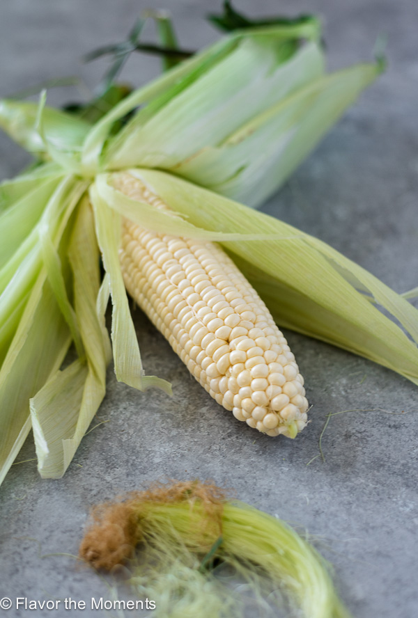 close up of partially shucked corn