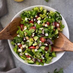 overhead shot of Greek chopped salad with wooden spoons