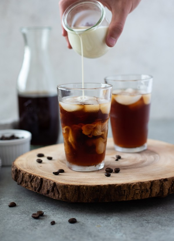 cold brew coffee recipe in glass with creamer pouring