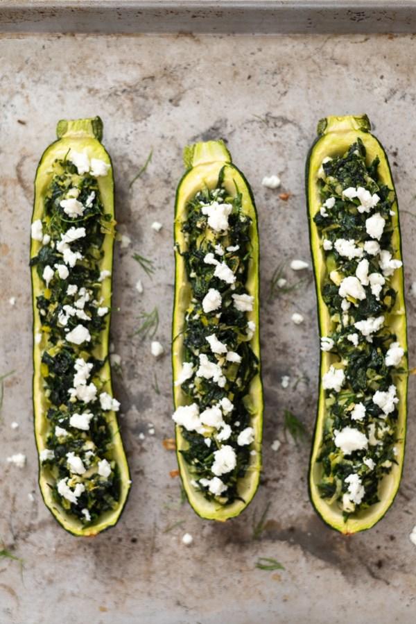 overhead shot of spanakopita stuffed zucchini boats on sheet pan