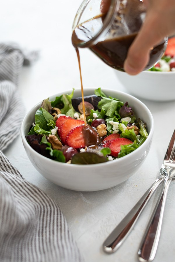 strawberry salad in white bowl with balsamic dressing drizzling