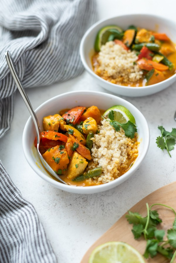 pumpkin curry in a bowl with quinoa and a spoon