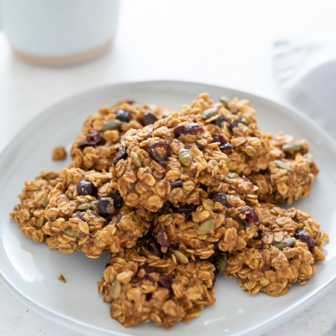 pumpkin breakfast cookies on a plate with coffee in the background