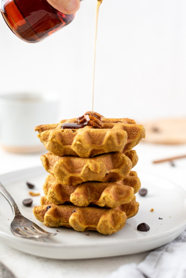 pumpkin oat flour waffles stacked with maple syrup drizzling over
