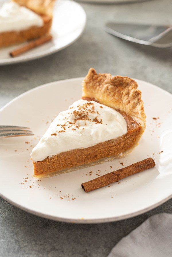front shot of slice of pumpkin pie from scratch topped with whipped cream and pumpkin pie spice