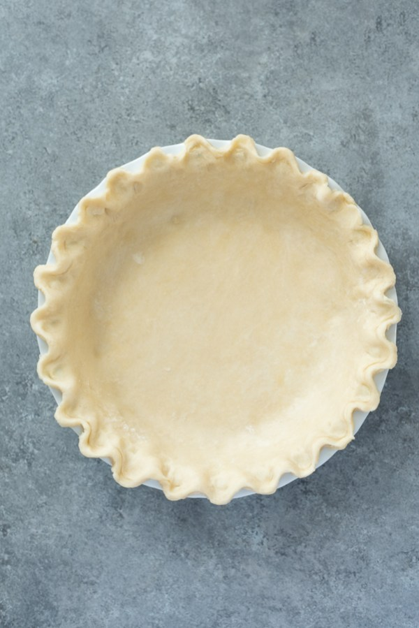 close up overhead shot of flaky pie crust in pie plate