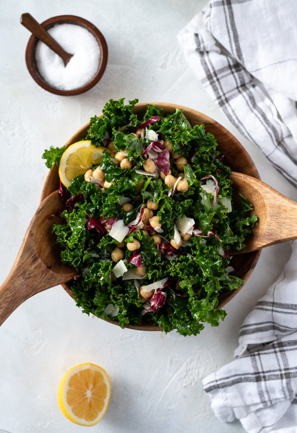 overhead shot of massaged kale salad with chickpeas and parmesan with wooden servers