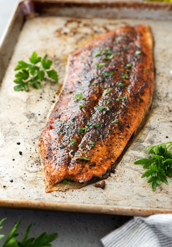 broiled salmon on baking sheet with chopped parsley on top