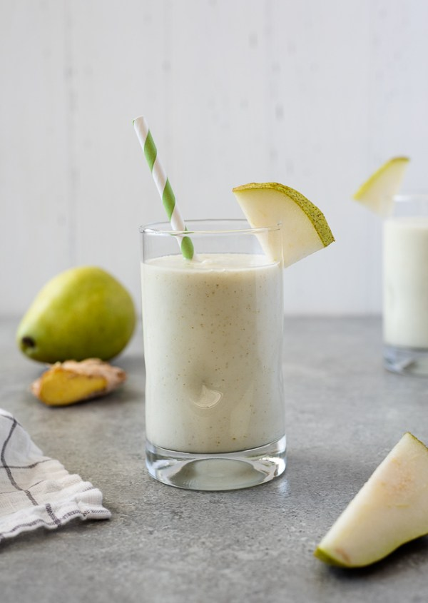 close up of pear smoothie with pear and ginger in the background