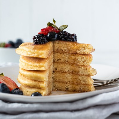stack of almond flour pancakes with berries on top and maple syrup dripping