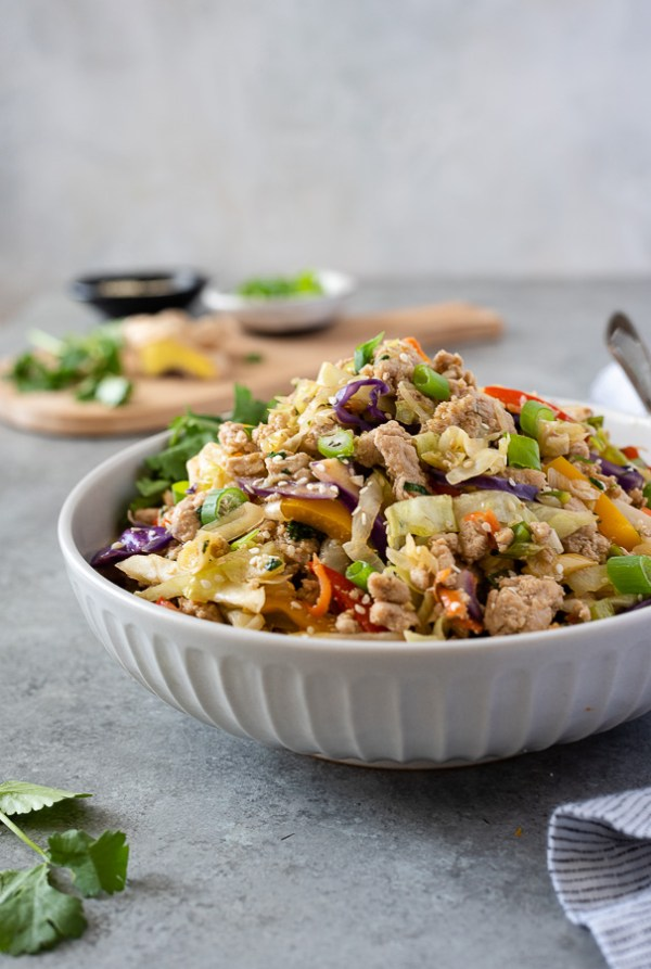 close up of egg roll in a bowl piled high in serving bowl