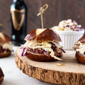 guinness corned beef sliders on serving platter with coleslaw alongside