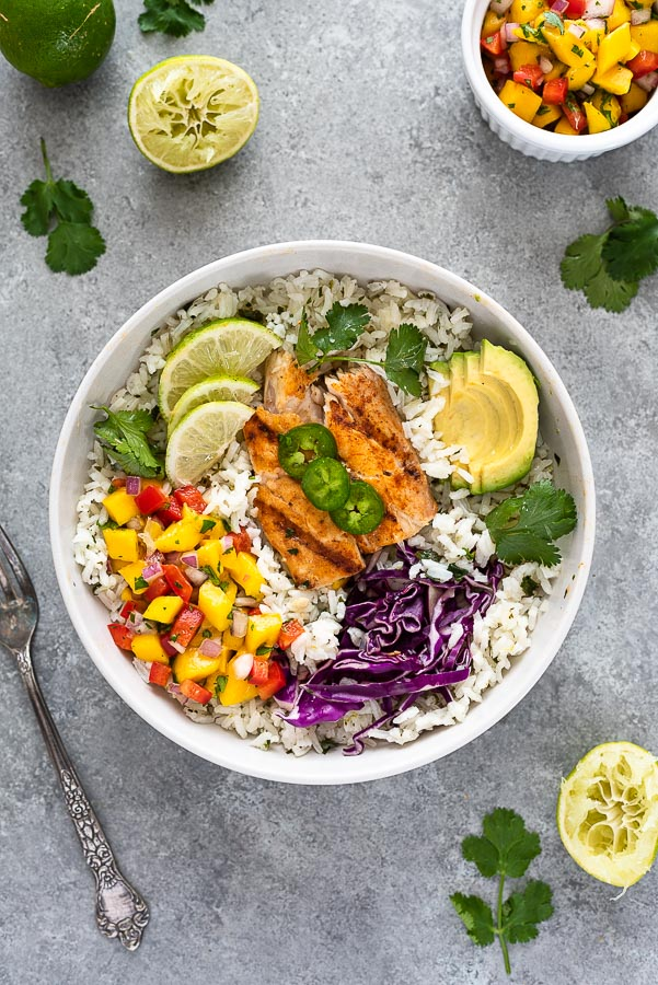 fish taco bowl in white bowl with salsa, cabbage and avocado