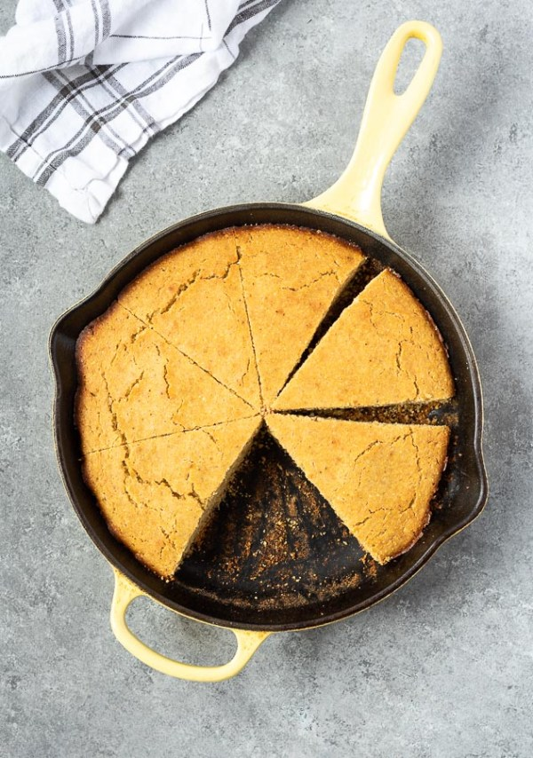 overhead shot of skillet cornbread in cast iron skillet cut into wedges