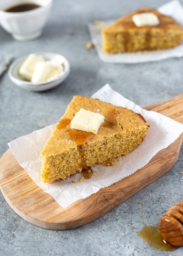 wedge of skillet cornbread with butter and honey on top