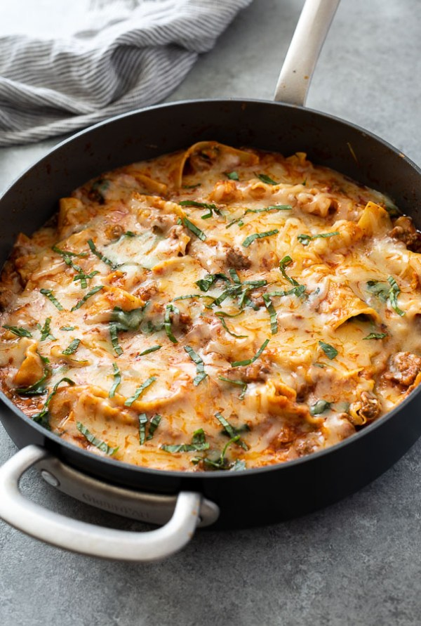 front shot of skillet lasagna in pan with basil on top