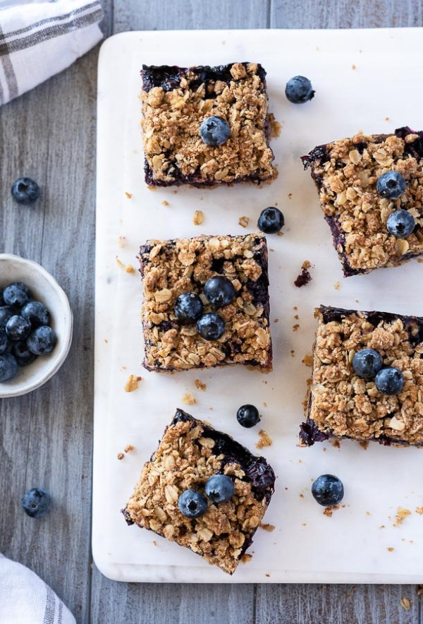 blueberry crumble bars scattered on a white server with blueberries