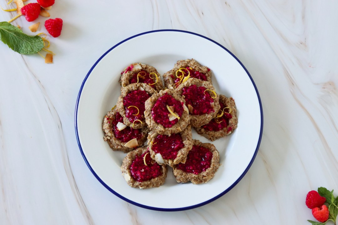 Flaxseed superfood cookies on a plate with fresh raspberries, lemon zest and toasted coconut flakes to garnish. Recipe by flavour-files.com