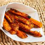 dill and onion roasted carrot fries in parchment paper cup