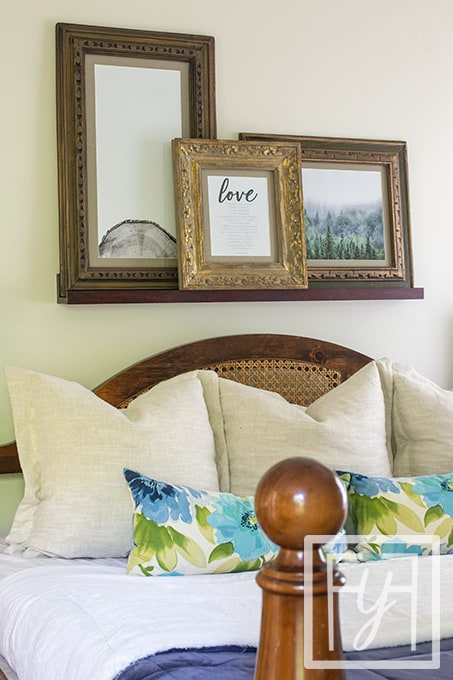 Three vintage frames resting on a hanging shelf over a king size bed