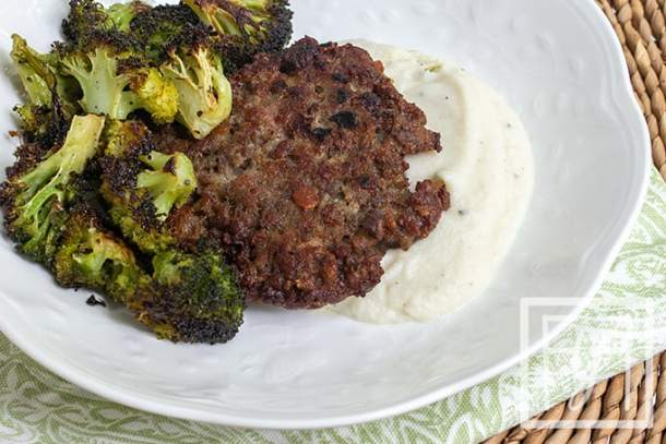 roasted garlic mashed cauliflower topped with a pork patty and broccoli