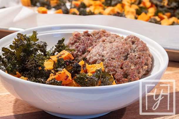 roasted sweet potatoes and kale chips in white bowl with sausage