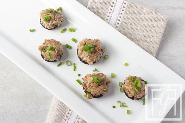 stuffed mushrooms with sausage on white plate