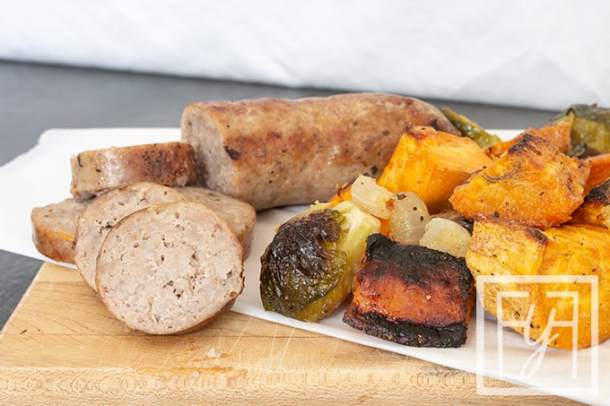 sheet pan bratwurst and roasted vegetables on cutting board