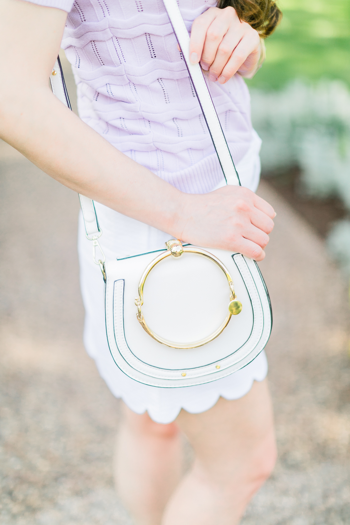 How to wear a short sleeve sweater in the spring by southern fashion blogger Stephanie Ziajka from Diary of a Debutante, lilac Cable Stitch short sleeve sweater, Lilly Pulitzer scalloped mini skirt, white Chloe Nile dupe bag, Chloe dupe bags, Kendra Scott mixed metal bangle set