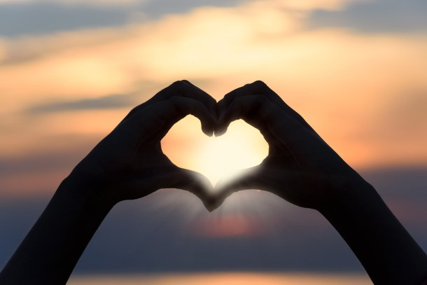 Hands forming a heart against a sunset sky to lift you up and help you learn from bad experiences
