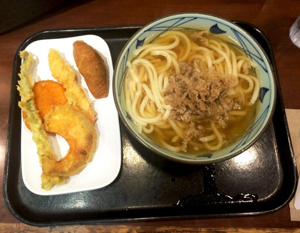 Bowl of Niku Udon with assorted tempura on the side at Marukame Udon for foods you must try in Waikiki