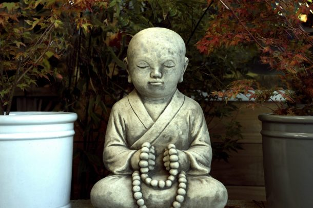 A small monk statue holding beads surrounded by potted plants