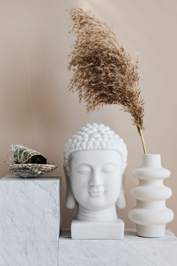 A mini indoor meditation garden with a small Buddha statue, sage, and a vase