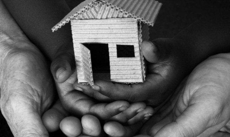 image of hands holding cardboard house indicating homeless shelter