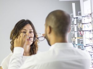 Woman trying on glasses in opticians