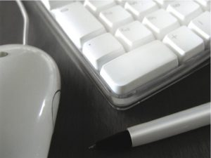 Cropped image of Mac keyboard and mouse and a pen
