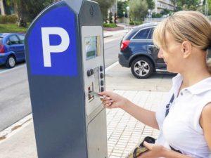 Woman paying at parking meter