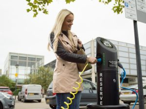 Woman using EV charger in car park