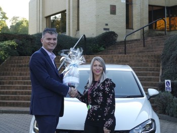 Nexus client development director Mike Palmer, presenting Acorn Stairlift's Jolene Shaw with a bottle of champagne to mark the milestone booking