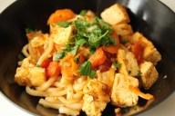asiatisch gewürzte Nudeln mit Gemüsepfanne, Tofu und Kräutern