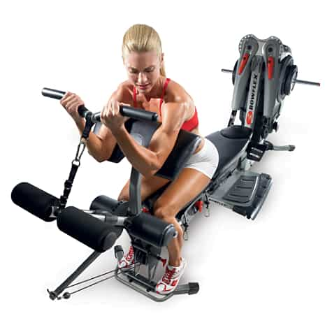 Very fit woman does arm curls on the bowflex revoltution